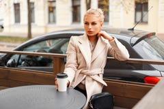 Bella donna alla moda in un cappotto d'avanguardia classico con un vetro immagine stock libera da diritti
