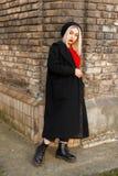 Bella donna alla moda in un cappotto nero con un jersey rosso immagini stock libere da diritti