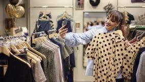 Bella donna allegra adulta che esamina il vestito dal pois in un negozio di vestiti e che prende selfie con su uno smartphone stock footage