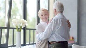 Bella donna anziana che esamina la macchina fotografica coppie amorose e felici che parlano in appartamento moderno video d archivio