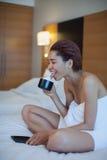 Bella donna in asciugamano sul caffè bevente del letto con panna montata Fotografia Stock Libera da Diritti
