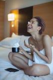 Bella donna in asciugamano sul caffè bevente del letto con panna montata Immagine Stock