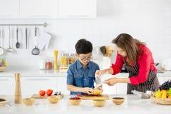 Bella donna asiatica in camicia rossa ed in grembiule nero gli che insegna fotografia stock