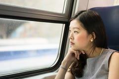 Bella donna asiatica che guarda dalla finestra del treno, con lo spazio della copia Fotografia Stock
