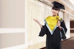Bella donna asiatica che per mezzo del cappuccio di graduazione e tenendo certifica Fotografia Stock Libera da Diritti