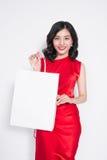 Bella donna asiatica che porta un vestito rosso con il sacchetto della spesa stan Fotografia Stock