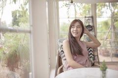 Bella donna asiatica che si rilassa nel salone domestico immagini stock libere da diritti