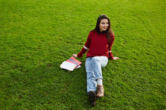 Bella donna asiatica che si rilassa sull'erba verde dopo gli esami di entrata in università spagnola Immagine Stock Libera da Diritti