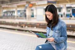 Bella donna asiatica che studia mappa alla stazione ferroviaria, con lo spazio della copia Fotografie Stock