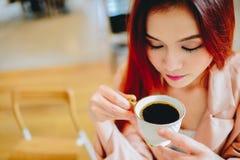 Bella donna asiatica che tiene una tazza di caffè in sua mano immagine stock
