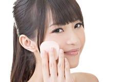 Bella donna asiatica che usando spugna cosmetica sul fronte fotografia stock libera da diritti