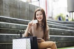 Bella donna asiatica con i sacchetti della spesa e una carta Fotografia Stock