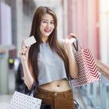 Bella donna asiatica con i sacchetti della spesa e una carta Immagini Stock Libere da Diritti