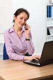 Bella donna asiatica di affari che per mezzo del telefono Immagine Stock