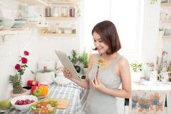 Bella donna asiatica felice che prepara alimento sano nel kitche fotografia stock libera da diritti