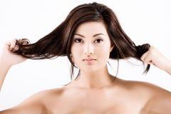 Bella donna asiatica naturale che tira capelli immagine stock