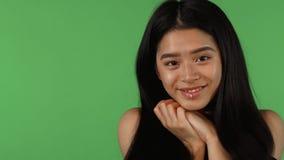 Bella donna asiatica sbalorditiva che sembra sveglia e felice su backgorund verde stock footage
