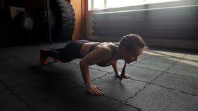 Bella donna atletica che fa spinta-UPS sul pavimento al rallentatore nella palestra stock footage