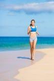 Bella donna atletica che funziona sulla spiaggia Immagini Stock Libere da Diritti