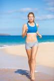 Bella donna atletica che funziona sulla spiaggia Fotografia Stock