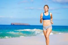Bella donna atletica che funziona sulla spiaggia Immagini Stock