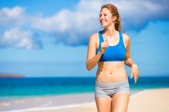 Bella donna atletica che funziona sulla spiaggia Fotografie Stock
