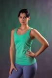 Bella donna atletica, condizione della donna di forma fisica, posante su un fondo grigio con una lampadina verde Fotografia Stock