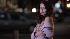 Bella donna attraente che esamina macchina fotografica nella città di notte, movimento lento video d archivio