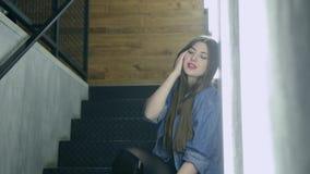 Bella donna attraente che posa sulla scala nera del ferro nello stile del sottotetto video d archivio