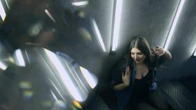 Bella donna attraente che posa sulla scala nera del ferro nello stile del sottotetto archivi video