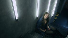 Bella donna attraente che posa sulla scala nera del ferro nello stile del sottotetto stock footage