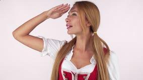 Bella donna bavarese in vestito dal dirndl che distoglie lo sguardo con la sua mano ai suoi occhi stock footage