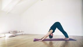 Bella donna bianca che fa yoga all'interno, vista laterale video d archivio