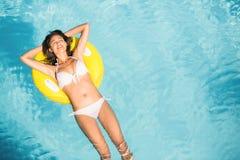 Bella donna in bikini bianco che galleggia sul tubo gonfiabile nella piscina immagine stock libera da diritti