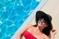 Bella donna in bikini rosso che si rilassa vicino alla piscina immagini stock libere da diritti