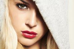Bella donna bionda in cappuccio. labbra rosse Fotografia Stock