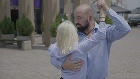 Bella donna bionda che balla ballo sensuale della salsa o di rumba con il forte esecutore maschio fuori nella via urbana - video d archivio