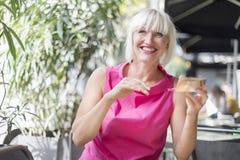 Bella donna bionda che compone facendo uso di uno specchio d'argento - Outdoo fotografia stock libera da diritti
