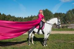 Bella donna bionda che monta un cavallo Fotografia Stock Libera da Diritti