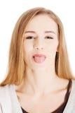 Bella donna bionda che mostra la sua lingua. Fotografia Stock