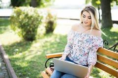Bella donna bionda che per mezzo del computer portatile mentre sedersi rilassata sul banco al parco di estate Immagini Stock