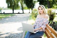 Bella donna bionda che per mezzo del computer portatile mentre sedersi rilassata sul banco al parco di estate Fotografia Stock