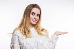 Bella donna bionda che porta maglione tricottato beige e che mostra il vostro prodotto Bella ragazza che indica il lato fotografia stock libera da diritti