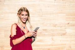 Bella donna bionda che sorride e che per mezzo del telefono cellulare po all'aperto Immagini Stock Libere da Diritti