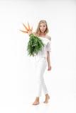 Bella donna bionda che tiene carota fresca con le foglie verdi su fondo bianco Salute e dieta Immagine Stock
