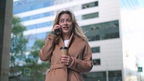 Bella donna bionda con caffè che parla sullo smartphone nella via video d archivio