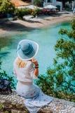 Bella donna bionda con il cappellino da sole blu ed i vestiti bianchi che si siedono davanti alla baia blu del villaggio tranquil fotografia stock libera da diritti