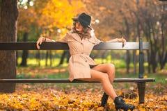 Bella donna bionda con il cappotto crema, gambe e black hat lunghi in una scena di autunno immagini stock