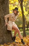 Bella donna bionda con il cappotto crema, gambe e black hat lunghi in una scena di autunno fotografia stock libera da diritti
