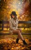 Bella donna bionda con il cappotto crema, gambe e black hat lunghi in una scena di autunno immagine stock